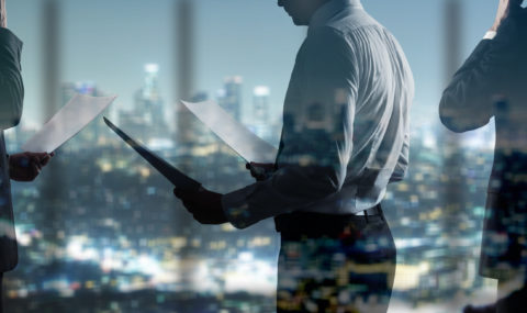 Financial city businessman holding papers superimposed over an abstract dark city scene.