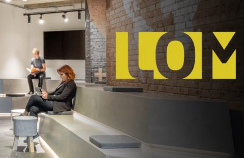 LOM logo with a stylish office interior background